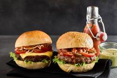 2 гамбургера на черной салфетке около погружения Стоковое Фото