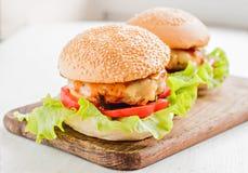 2 гамбургера положенного на деревянную доску Стоковая Фотография