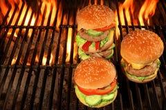 Гамбургеры Cheeseburgers домодельные на горячем пламенеющем гриле BBQ Стоковые Фотографии RF