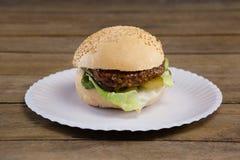 Гамбургер в плите на деревянном столе Стоковые Изображения RF