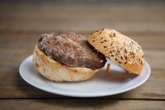 Гамбургер в плите на деревянном столе Стоковое Изображение