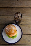 Гамбургер в плите с стеклом холодного напитка Стоковая Фотография
