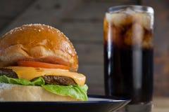 Гамбургер в плите с стеклом холодного напитка Стоковые Изображения