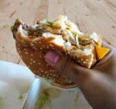 Гамбургер в руке Стоковые Изображения