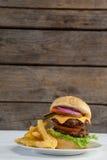 Гамбургер и француз жарят в плите на деревянном столе Стоковые Изображения