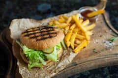 Гамбургер и француз жарят с соусом на деревянной доске Стоковое Изображение RF