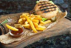 Гамбургер и француз жарят с соусом на деревянной доске Стоковые Изображения