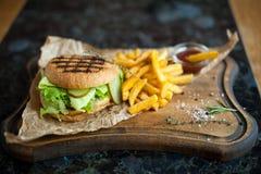 Гамбургер и француз жарят с соусом на деревянной доске Стоковые Изображения RF