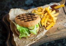 Гамбургер и француз жарят с соусом на деревянной доске Стоковые Фото