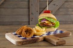 Гамбургер, кольцо лука и фраи француза на прерывая доске Стоковое Изображение RF