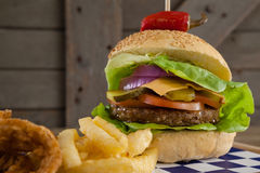 Гамбургер, кольцо лука и фраи француза на прерывая доске Стоковая Фотография