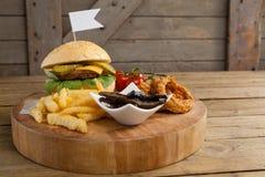 Гамбургер, кольцо лука и фраи француза на прерывая доске Стоковые Изображения RF