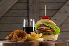 Гамбургер, кольцо лука и фраи француза с холодным напитком на прерывая доске Стоковая Фотография