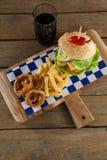 Гамбургер, кольцо лука и фраи француза с холодным напитком на прерывая доске Стоковая Фотография RF