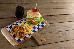 Гамбургер, кольцо лука и фраи француза с холодным напитком на прерывая доске Стоковое Изображение RF