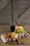 Гамбургер, кольцо лука и фраи француза с холодным напитком на прерывая доске Стоковые Изображения