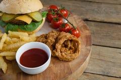 Гамбургер, кольцо лука, томатный соус, томат вишни и фраи француза на прерывая доске Стоковые Фотографии RF