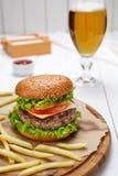 Гамбургер с зажаренными мраморизованными говядиной, томатом, сыром, салатом и фраями Стоковое Изображение RF