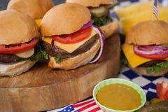 Гамбургер с соусом мустарда на деревянной доске Стоковое фото RF