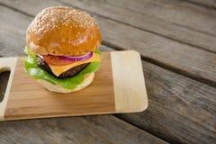 Гамбургер с сыром на разделочной доске Стоковые Фото