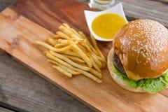 Гамбургер с фраями и погружение на разделочной доске Стоковая Фотография RF