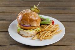 Гамбургер, фраи француза и салат в плите на деревянном столе Стоковые Изображения