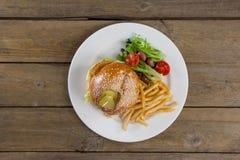 Гамбургер, фраи француза и салат в плите на деревянном столе Стоковые Фотографии RF