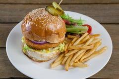 Гамбургер, фраи француза и салат в плите на деревянном столе Стоковые Изображения RF