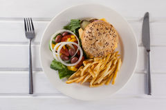 Гамбургер, французские фраи, и салат в плите на деревянном столе Стоковое Изображение RF