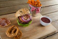 Гамбургер, французские фраи, кольцо лука и томатный соус на прерывая доске Стоковая Фотография RF
