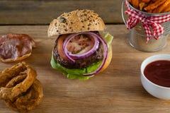 Гамбургер, французские фраи, кольцо лука и томатный соус на прерывая доске Стоковое фото RF