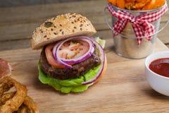 Гамбургер, французские фраи, кольцо лука и томатный соус на прерывая доске Стоковое Изображение RF