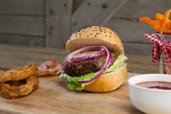 Гамбургер, французские фраи, кольцо лука и томатный соус на прерывая доске Стоковая Фотография