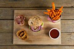Гамбургер, французские фраи, кольцо лука и томатный соус на прерывая доске Стоковое Фото