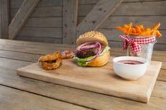 Гамбургер, французские фраи, кольцо лука и томатный соус Стоковые Фотографии RF