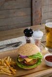 Гамбургер, французские фраи, томатный соус и стекло пива на прерывая доске Стоковое фото RF