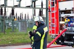 Гамбург, Германия - 18-ое апреля 2013: HDR - вождь пожарного в действии около пожарной машины Стоковые Изображения