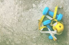 Гантели бирюзы с измеряя лентой и желтым яблоком на конкретной предпосылке Открытый космос для вашего текста изолированная принци Стоковое Фото