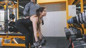 Гантели в спортзале - близкое поднимающее вверх спортсмена женщины поднимаясь Стоковое Изображение RF