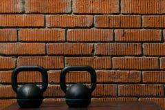 2 гантели для спорт в спортзале на предпосылке оранжевой кирпичной стены Стоковые Фото