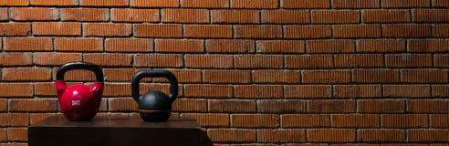 2 гантели для спорт на постаменте около кирпичной стены, длинного фото Стоковое фото RF