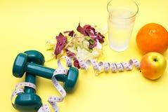 Гантели для спорт Салат и рулетка фитнеса на желтой таблице Стоковые Изображения