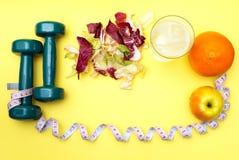 Гантели для спорт Салат и рулетка фитнеса на желтой таблице Стоковое Изображение