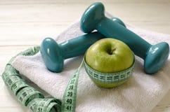 Гантели, зеленое яблоко, полотенце, сантиметр на белом деревянном backgr Стоковое Фото