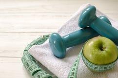 Гантели, зеленое яблоко, полотенце, сантиметр на белом деревянном backgr Стоковое Изображение RF