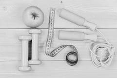 Гантели, измеряя лента, веревочка скачки и яблоко, взгляд сверху Штанги и сантиметр около инструментов для потери веса разминка Стоковые Изображения
