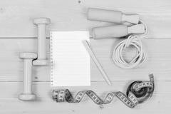 Гантели, измеряя лента, веревочка скачки, тетрадь и ручка, взгляд сверху Стоковое фото RF
