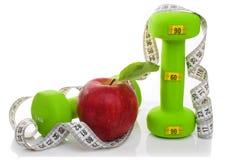 2 гантели, красное яблоко, измеряя лента на белой предпосылке диетпитание принципиальной схемы Стоковая Фотография RF
