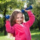 Гантели маленькой девочки поднимаясь Стоковые Фотографии RF