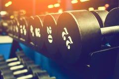 Гантели металла на железной стойке в зале спорт, конце-вверх на черной предпосылке Стоковое Фото